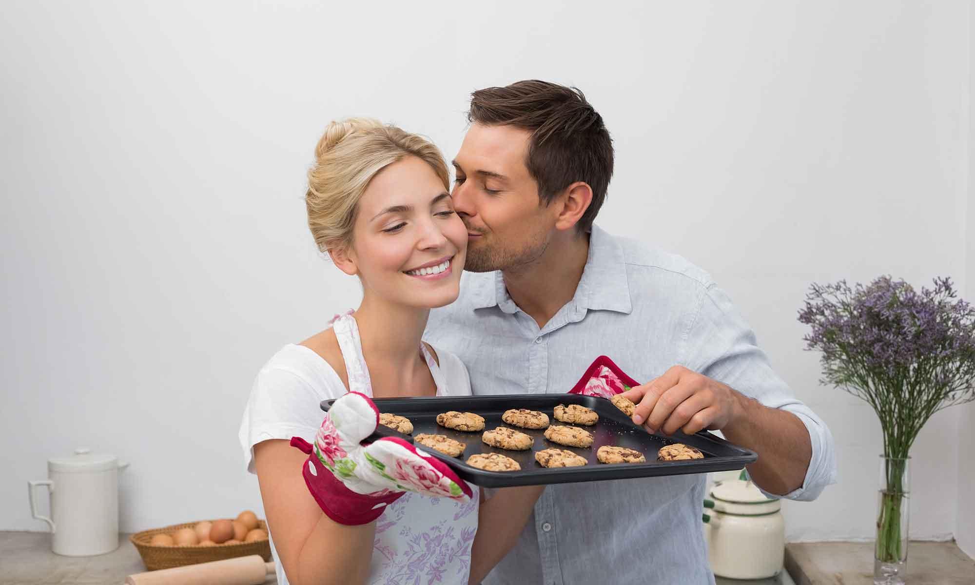 man kust vrouw met bakplaat vol koekjes