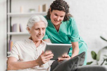 Oude dame en verpleegster met tablet