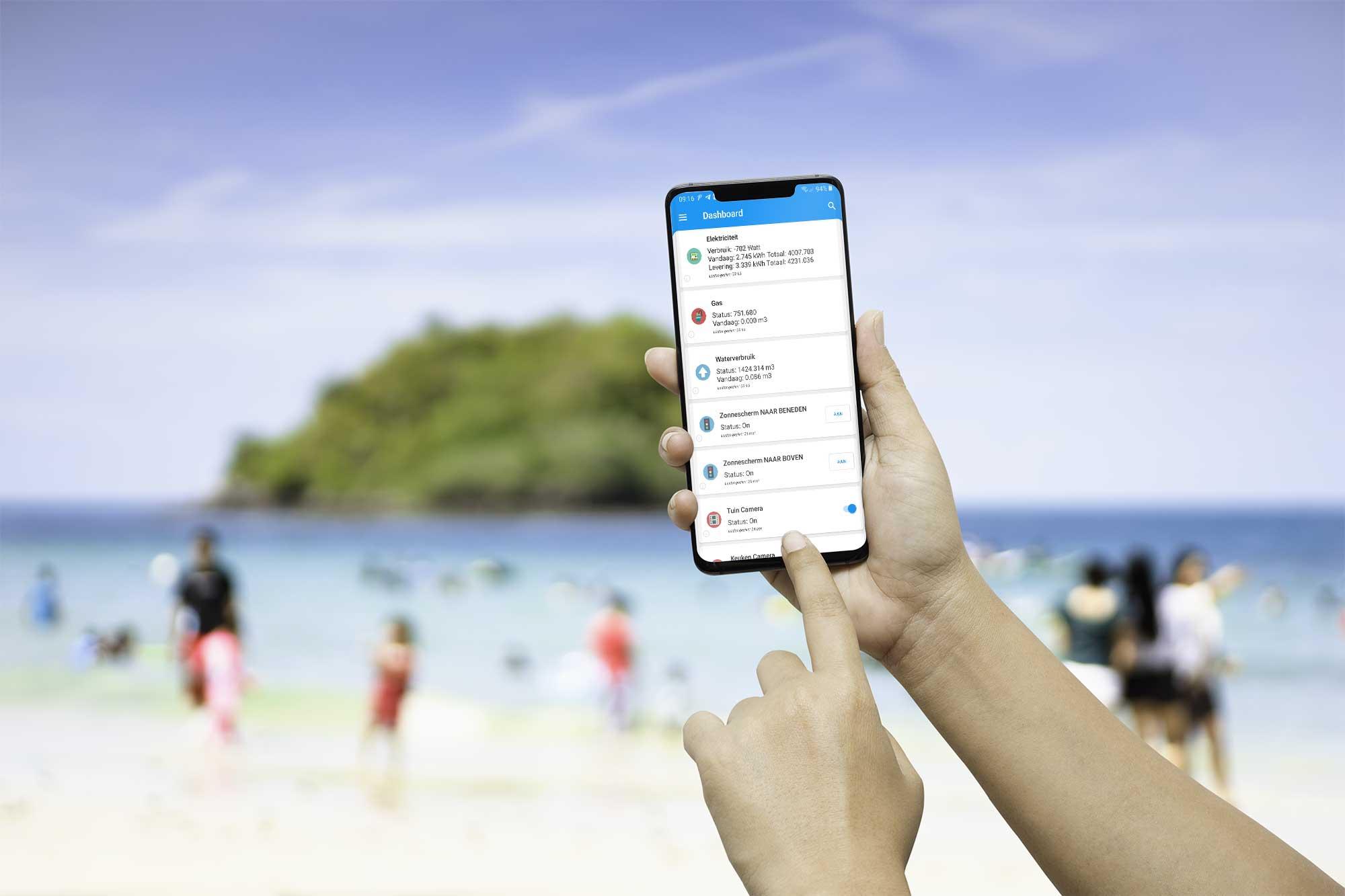 Hand met smartphone/Domoticz op het strand